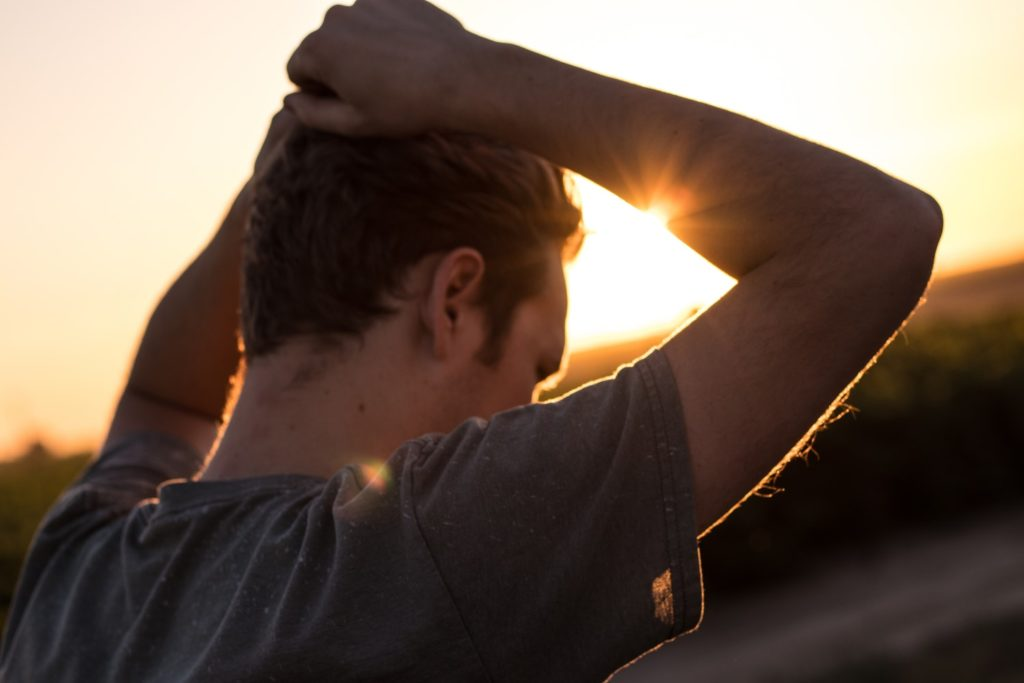 A man stands in the fading sunlight fixing his hair alone