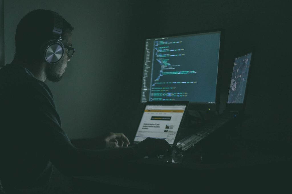 a man at his computer in a dark room coding