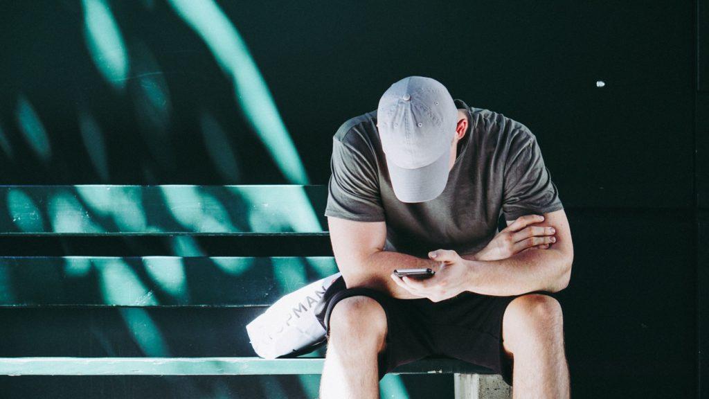 a man checks his phone, head down, hat on