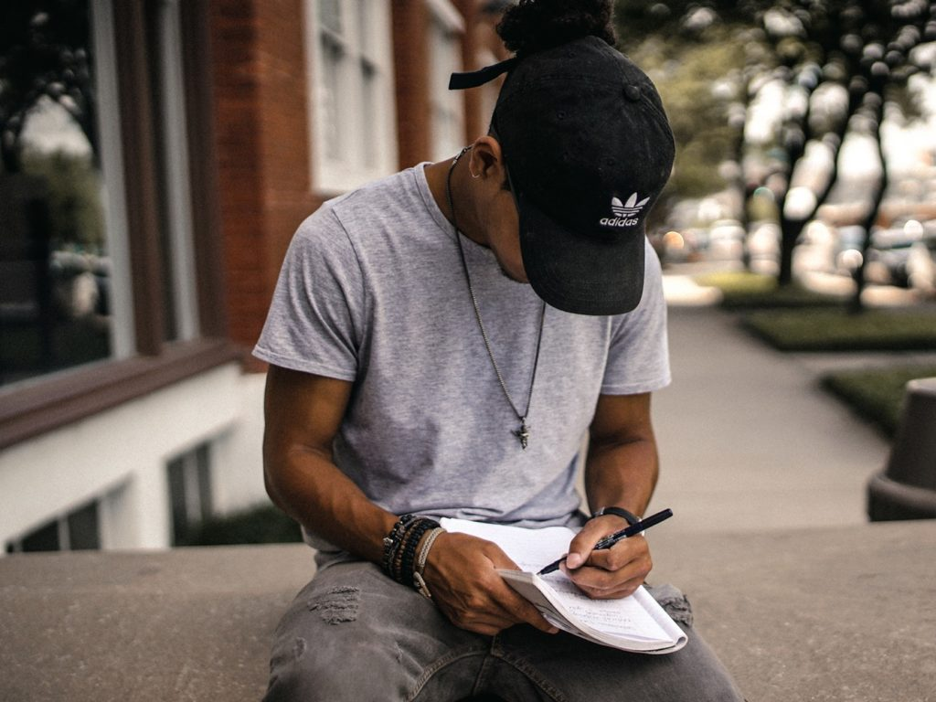 a man in a cap writes in a notebook