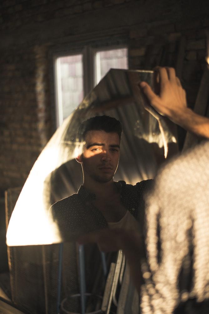 a man looks at himself in broken mirror shard