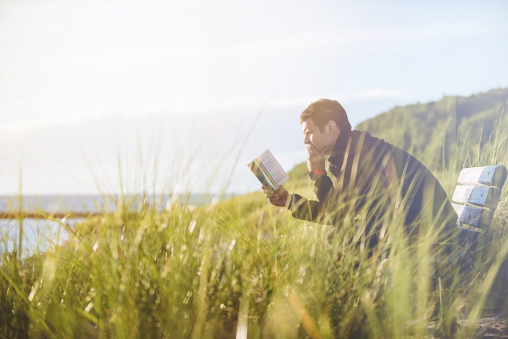 a man reads a book to learn more about hair growth