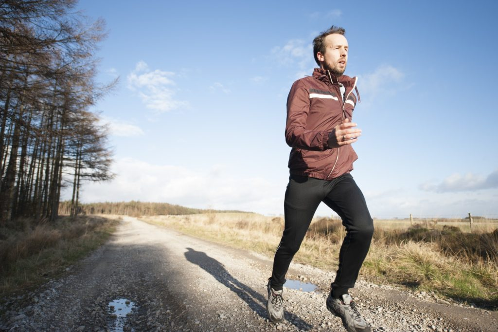 a man runs along a gravel road in the country