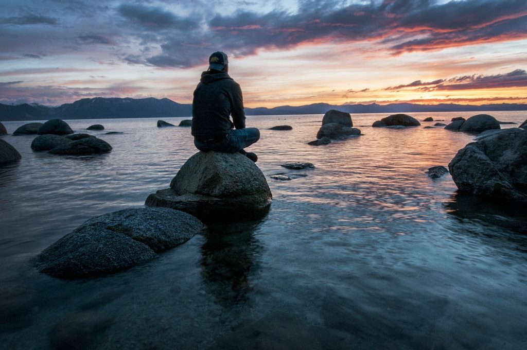 a man sits on a rock in the ocean