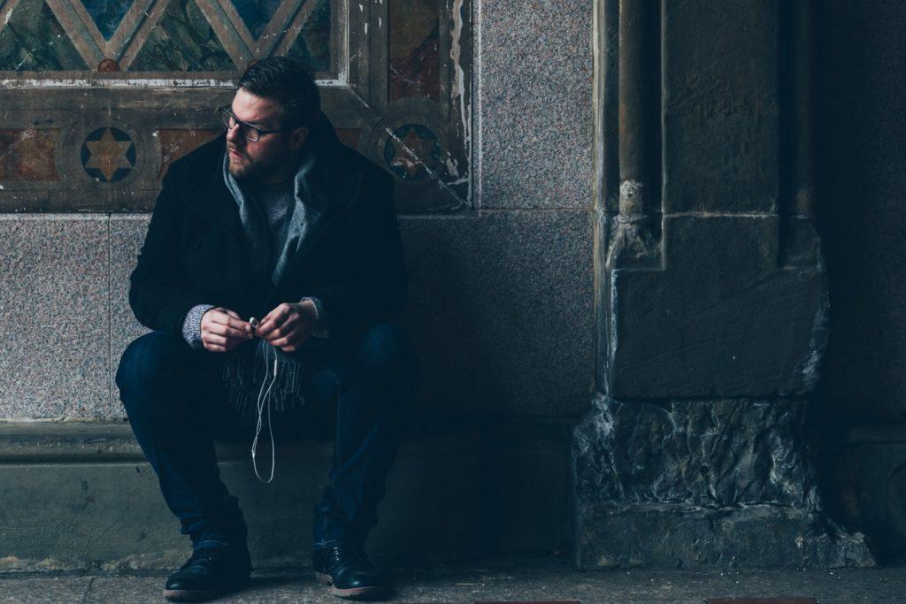 a man sits on the sidewalk