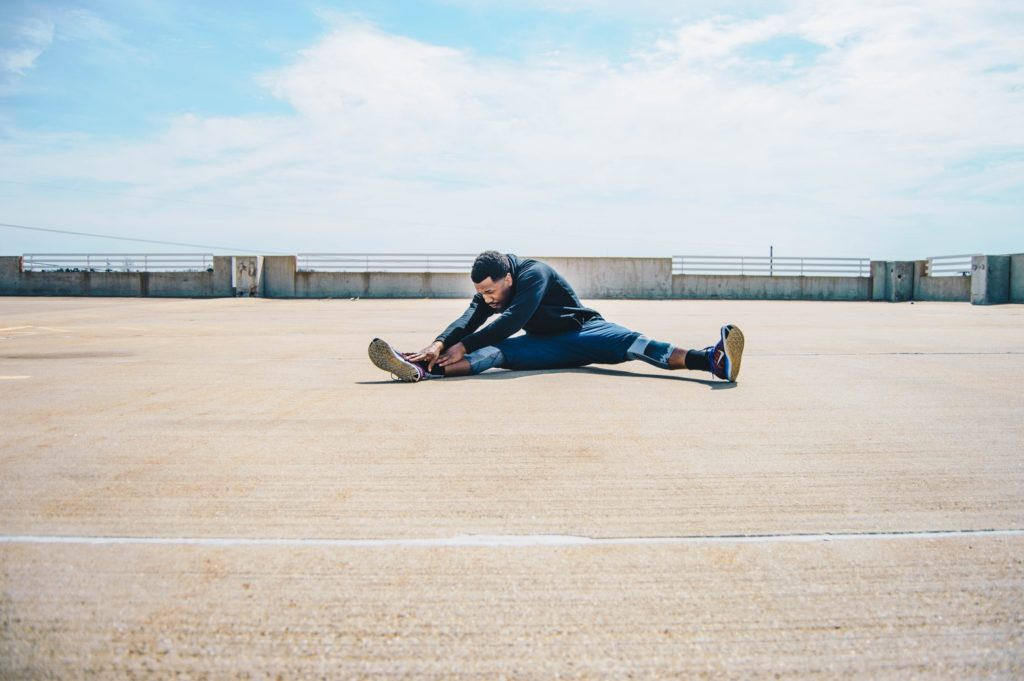 a man stretches at the top of a parking structure