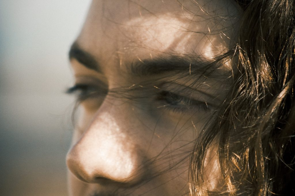 close up of mans face with hair tumbling into eyes