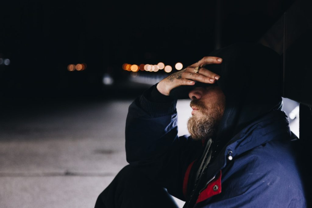 depressed man sits on the ground with hand shielding forehead