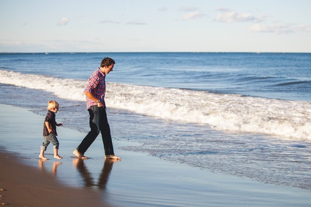 father and son walk on beach