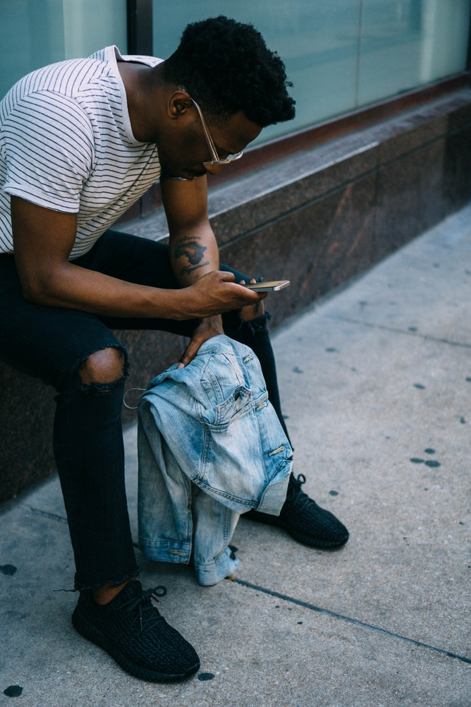 man looking at phone on city street, stressed about hair loss