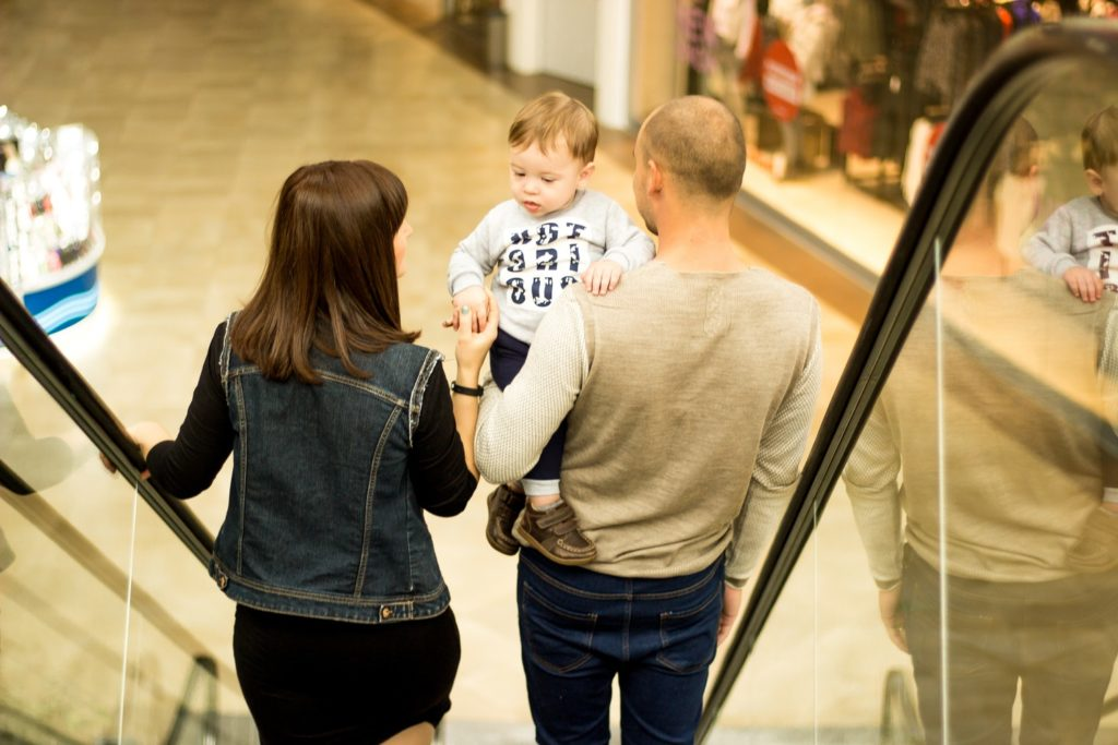 man woman and kid on escalator
