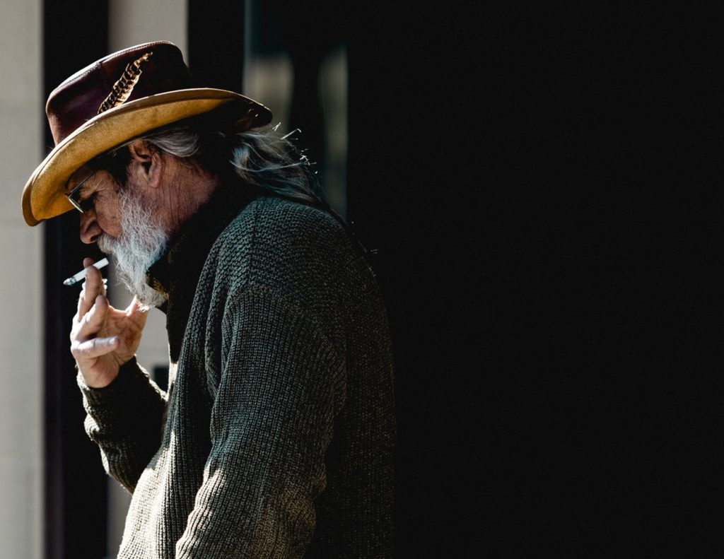 older man smokes a cigarette in a cowboy hat