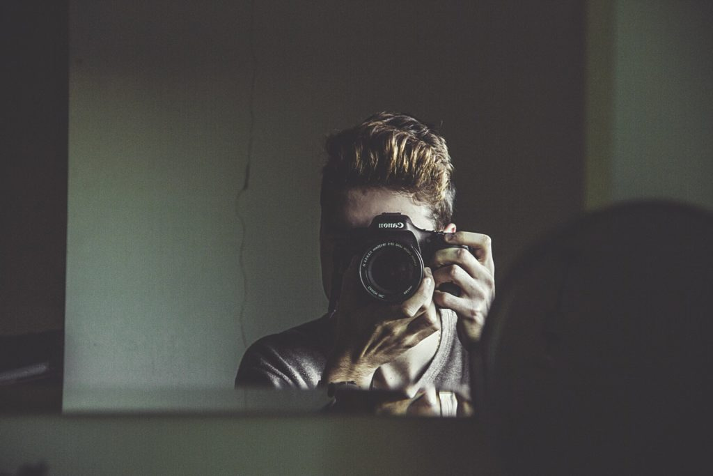 man takes a photo of himself in the mirror