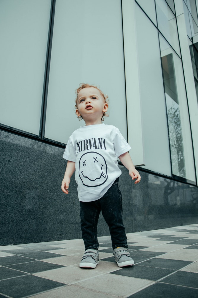 a baby in a Nirvana t-shirt stands on a city sidewalk