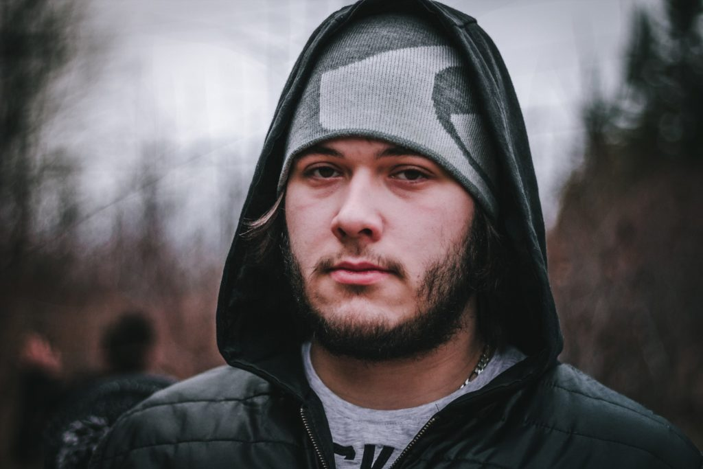 a man wearing a beanie and a hoodie