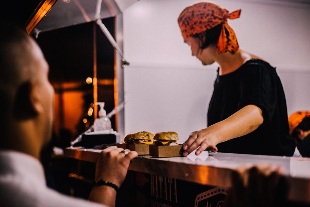 a woman serves a couple of burgers at a stand outdoors