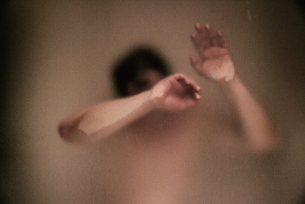 a guy stuck in a misty shower touches the glass door