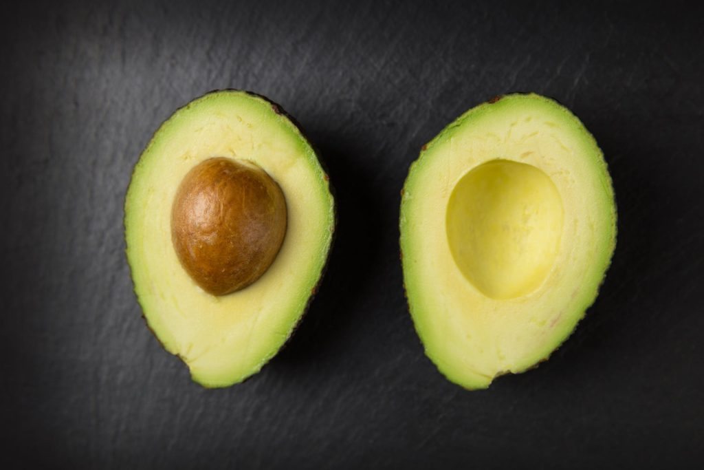 two halves of a sliced avocado on a black surface