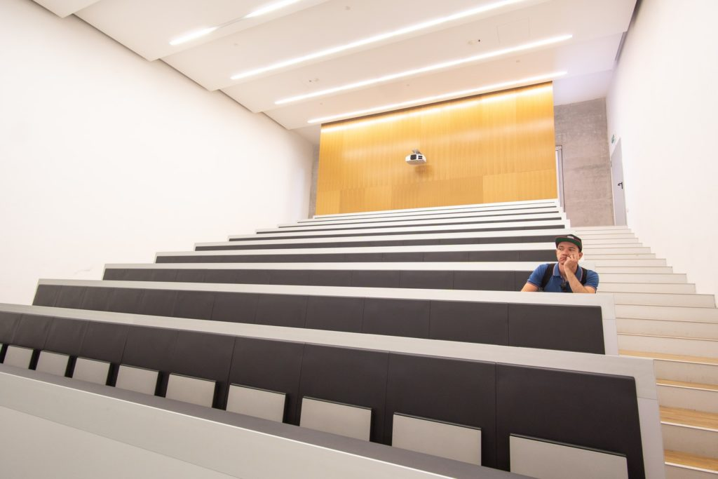 a man sits in an empty college lecture room