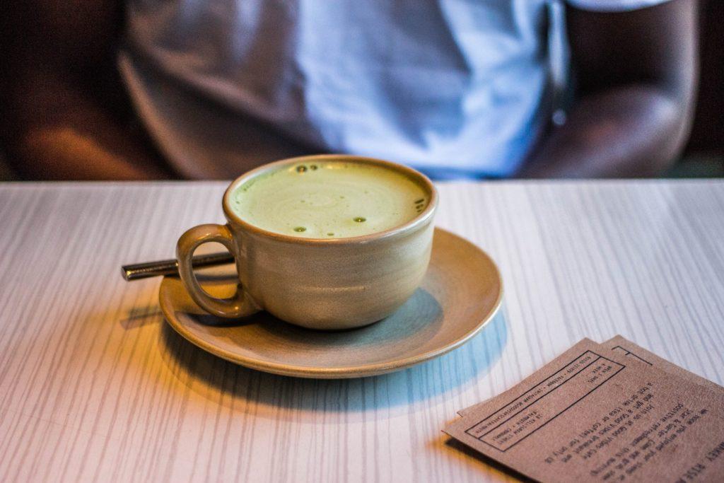 a green tea latte sits before a man
