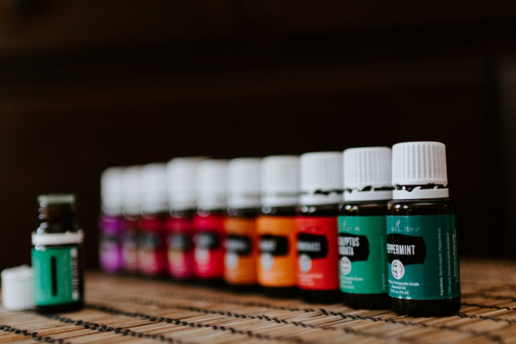 a row of colorefully labeled essential oils, the only one in focus being peppermint oil